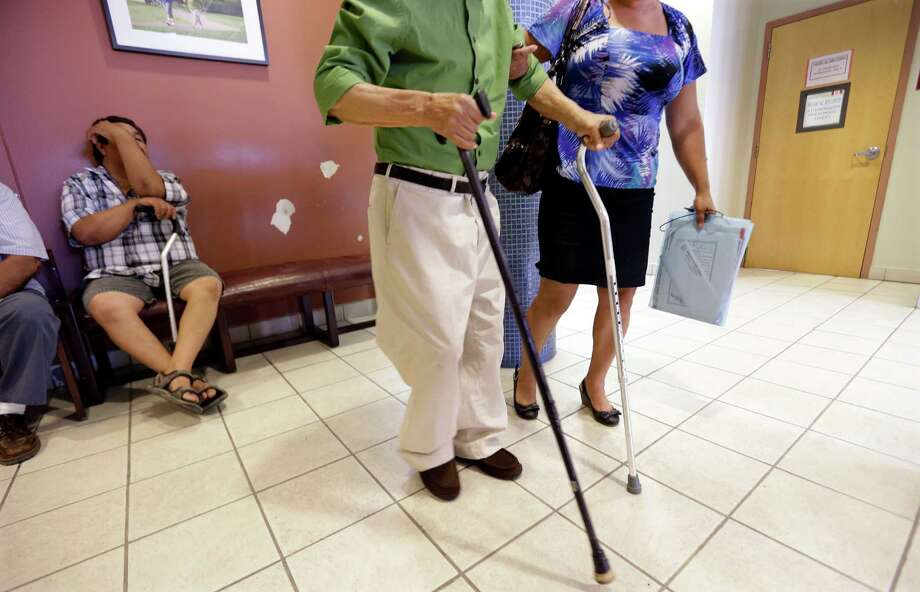 A patient gets help in the waiting room of a clinic. Many insurance companies have been de-emphasizing or withdrawing altogether from the long-term care insurance market. Scott Burns wonders if this is something to worry about. Photo: Eric Gay, STF / AP