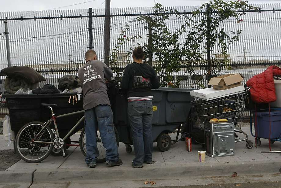 Homeless men tend to their belongings around the time of a September sweep under Interstate 280. Photo: Liz Hafalia, The Chronicle