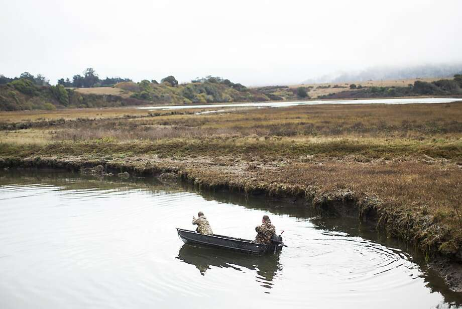 Two waterfowl hunters, whose names were not provided, navigate in a boat after hunting at Tomales Bay Ecological Reserve in Bivalve, Calif. on Saturday, Nov. 17, 2012. A newly-formed environmental group called Action Tomales Bay is seeking to petition the California Department of Fish and Game to stop waterfowl gaming in the Reserve. Though waterfowl gaming is currently legal and regulated, members of the action argue that the gaming creates unacceptable noise disturbances during early morning and evening hours and puts recreational users of the bay at risk. Hunters, however, reason that hunting in the reserve has been going on safely for generations and participants are just as environmentally conscious as their opponents. Photo: Stephen Lam, Special To The Chronicle