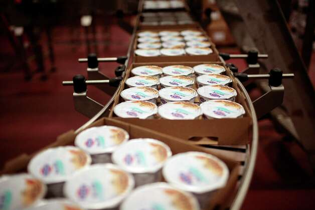 Yogurt whirs by on the assembly line at Fage USA Dairy Industry in Johnstown, N.Y., Jan. 6, 2012. Sales of Greek yogurt are booming, a benefit of the perception that the food is healthier than regular yogurt and other snacks, so leading brands are expanding their operations and the production jobs they entail. (Nathaniel Brooks/The New York Times) Photo: NATHANIEL BROOKS / NYTNS