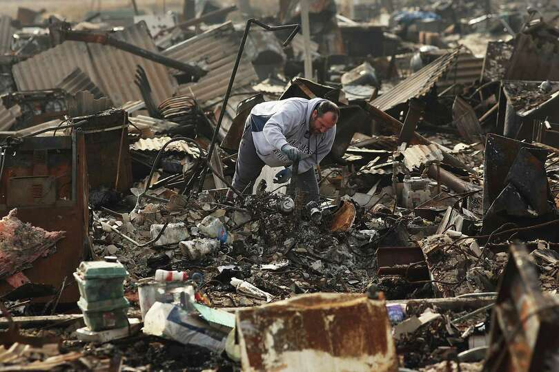 A man searches through the remains of his home December 4, 2012 in the Breezy Point neighborhood of