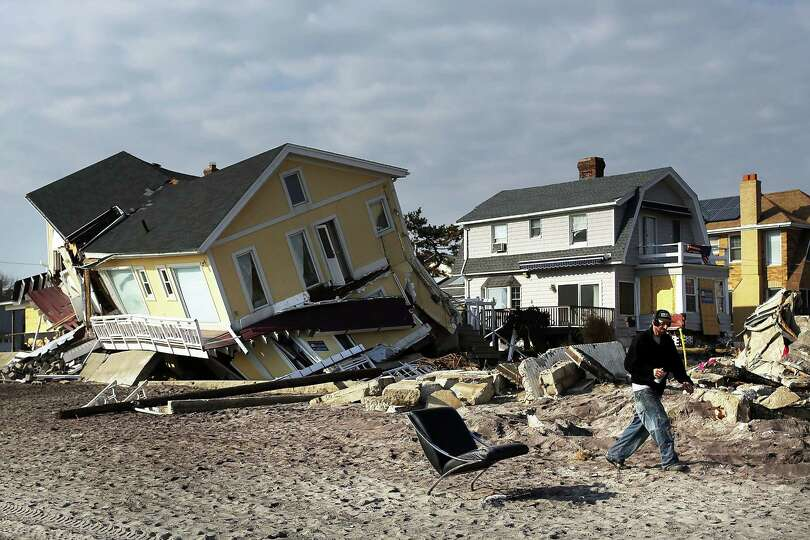 A man walks by destroyed homes along the beach December 4, 2012 in the Rockaway neighborhood of the