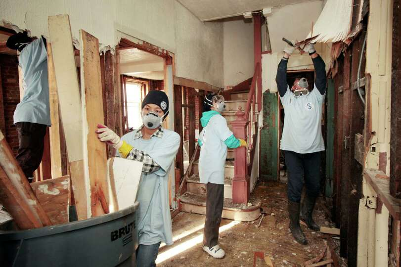 Riho Katsuta, left, carries debris from a home in the Far Rockaways section of New York with fellow