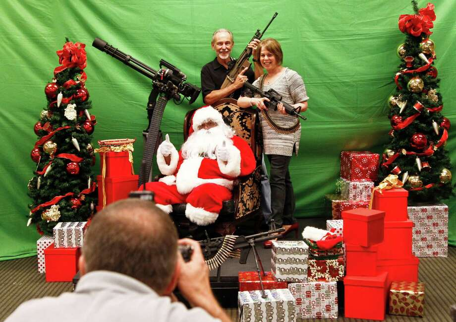 "Photographer Gordon Murray, foreground, takes a picture of Ron Ingram, top, and Barbara Ingram, right, as they pose with Santa at the third annual ""Santa and Machine Guns"" event at the Scottsdale Gun Club Dec. 2, 2012, in Scottsdale, Ariz. Photo: Ross D. Franklin, Associated Press / AP"