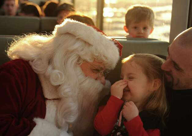 Santa Claus visits with Madilyn Bristow and her father Mike Bristow on the 2012 Alaska Railroad Holiday Train as it cruises along the Turnagain Arm to Indian and back to Anchorage, Alaska on Saturday, Dec. 1, 2012. The train featured a choir, a band, a magician and Santa and Mrs. Claus. The railroad has 4 holiday trains scheduled this year and the seats are sold out. Photo: Bob Hallinen, Associated Press / Anchorage Daily News