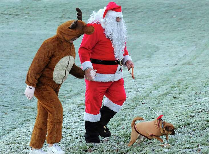 People dressed in a Santa Claus and a reindeer costume walk with their dog at the Great Nottingham S