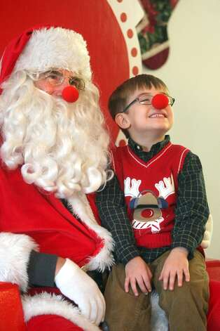 Peyton Milleson,4, of Kingston shows off his Rudolph nose as he sits with Santa at Santa's Workshop in Kingston on Saturday, Dec. 1, 2012. The event is sponsored by the Kingston Kiwanis. Photo: Larry Steagall, Associated Press / KITSAP SUN