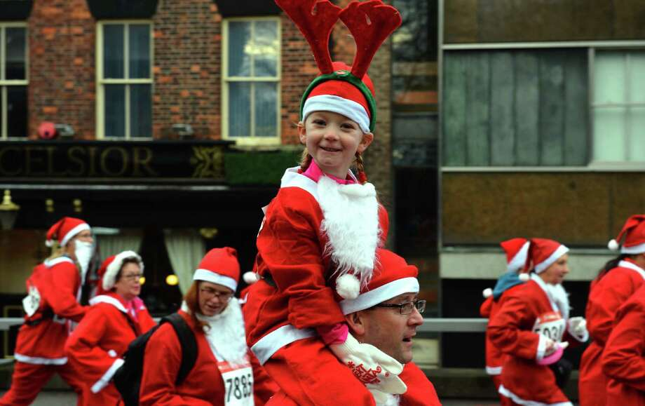 Runners dressed in Father Christmas costumes take part in the annual five kilometer Santa Dash in Liverpool, north-west England, on December 2, 2012. Many runners wear a blue suit, usually supporters of Everton FC, who refuse to run in the colours of their city rivals Liverpool FC. Photo: PAUL ELLIS, AFP/Getty Images / AFP