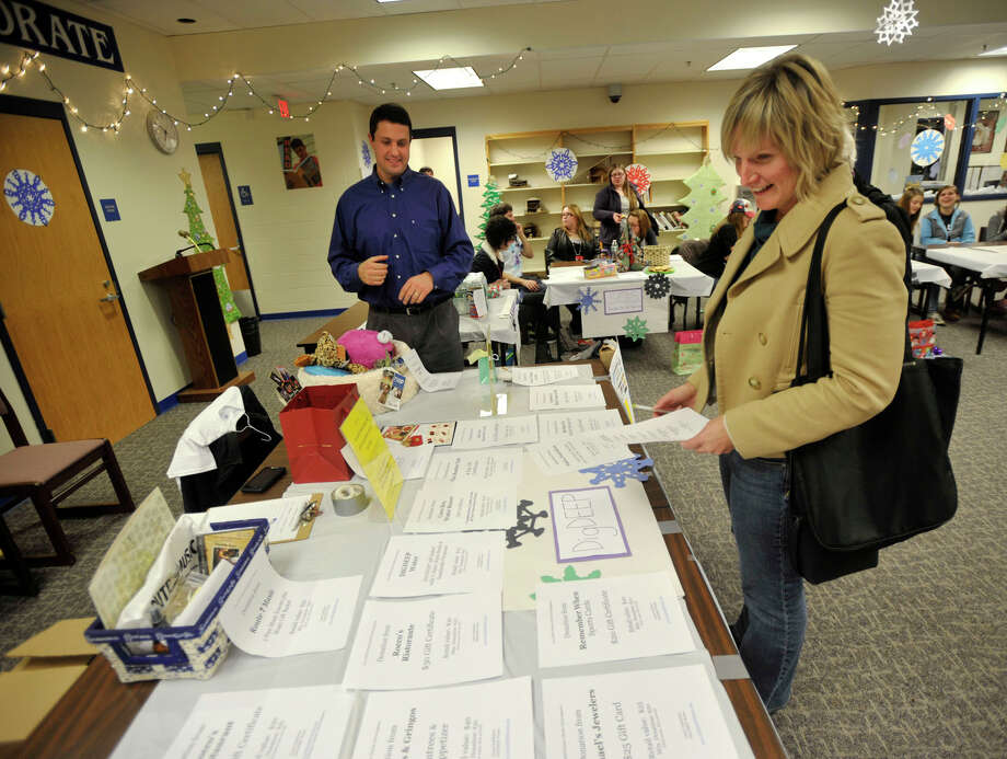 Judy Grady looks over the selection of items she could buy from David Plaue to benefit DIGDEEP Water, a human rights organization that believes everyone deserves clean drinking water, during the Winter Charity Extravaganza at Brookfield High School on Tuesday, Dec. 4, 2012. Photo: Jason Rearick / The News-Times