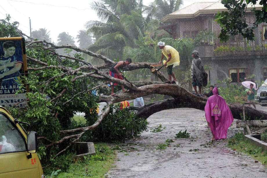 Workers clear a road with a fallen tree after Typhoon Bophal hit the city of Tagum, Davao del Norter province, on the southern island of Mindanao on December 4, 2012. Typhoon Bopha smashed into the southern Philippines early December 4, as more than 40,000 people crammed into shelters to escape the onslaught of the strongest cyclone to hit the country this year. Photo: AFP, AFP/Getty Images / cell:(63)9164168878             email:djcsantos@yahoo.com