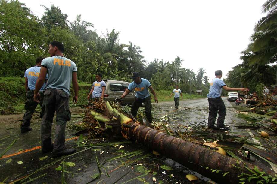 Philippine National Police clear a highway of toppled coconut trees after Typhoon Bopha made a landfall in Compostela Valley in southeastern Philippines Tuesday Dec. 4, 2012. A Philippine governor says at least 33 villagers and soldiers have drowned when torrents of water dumped by the powerful typhoon rushed down a mountain, engulfing the victims and bringing the death toll from the storm to about 40. Photo: Karlos Manlupig, Associated Press / AP