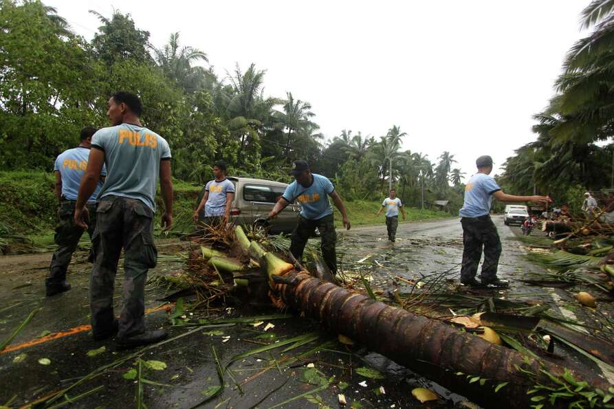 Philippine National Police clear a highway of toppled coconut trees after Typhoon Bopha made a landf