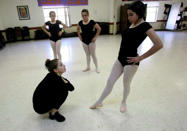 Lydia Relle, an instructor from the Ballet Conservatory of South Texas critiques Idiana Navarro, 13, ballet technique as Ximena Saenz and Persefanie Guerrero watch at KIPP Camino Academy. The conservatory provides all these children with proper ballet attire, and the class is free of charge. Photo: Helen L. Montoya, San Antonio Express-News / ©SAN ANTONIO EXPRESS-NEWS