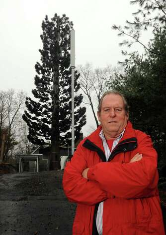 "John Hartwell stands near the new ""tree"" style cell tower and the ""flagpole"" style cell tower at the site behind his Ritch Ave. home in the Byram section of Greenwich, Conn. on Tuesday, Dec. 4, 2012. Photo: Cathy Zuraw / Stamford Advocate"