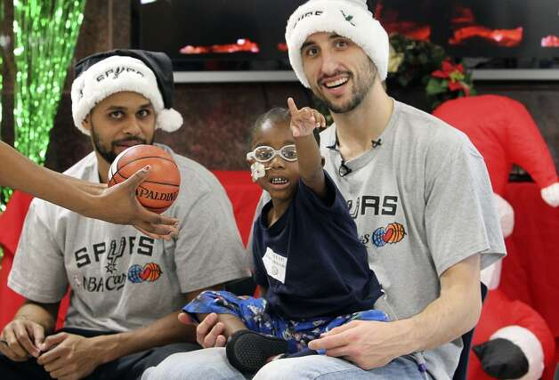 Edwin James, 4, gestures toward the cameras while posing for a photo with Spurs players Manu Ginobili (center) and Patty Mills at the Children's Hospital of San Antonio on Tuesday, Dec. 4, 2012. (Kin Man Hui / San Antonio Express-News)
