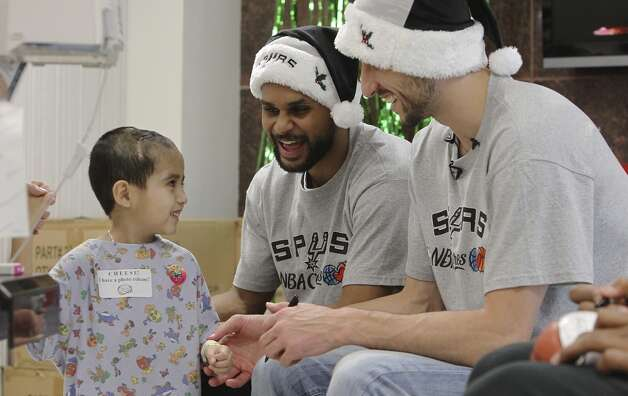 Julian Munoz, 5, returns a smile at Spurs players Manu Ginobili (right) and Patty Mills at the Children's Hospital of San Antonio on Tuesday, Dec. 4, 2012. (Kin Man Hui / San Antonio Express-News)