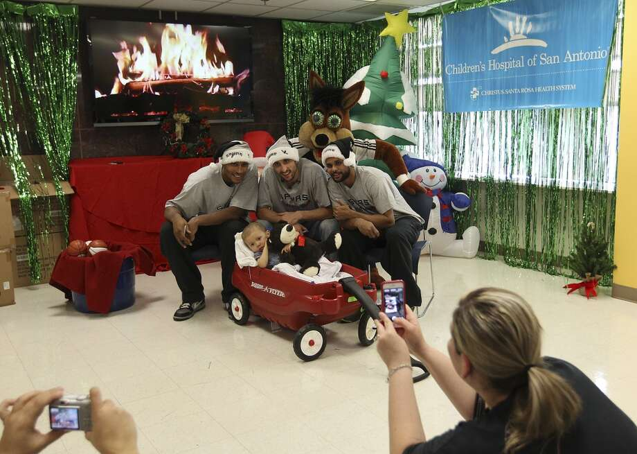 Spurs players Boris Diaw (from left), Manu Ginobili and Patty Mills along with the Spurs Coyote pose for a photo with Roman Paez, 2, at the Children's Hospital of San Antonio on Tuesday, Dec. 4, 2012.  (Kin Man Hui / San Antonio Express-News)