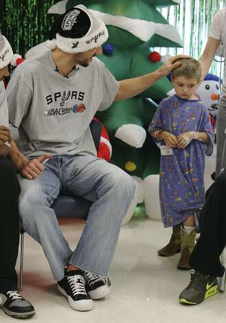 Spurs guard Manu Ginobili caresses the head of Baylor Scott, 5, before a photo shoot at the Children's Hospital of San Antonio on Tuesday, Dec. 4, 2012. (Kin Man Hui / San Antonio Express-News)