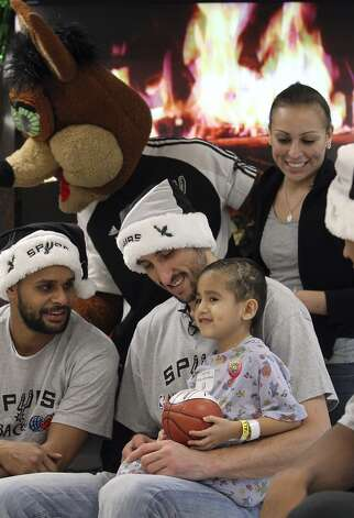 Julian Munoz, 5, sits on the lap of Spurs guard Manu Ginobili while joined by Spurs guard Patty Mills, the Spurs Coyote and Munoz's mother, Vanessa Cortinas, for a photo at the Children's Hospital of San Antonio on Tuesday, Dec. 4, 2012. (Kin Man Hui / San Antonio Express-News)