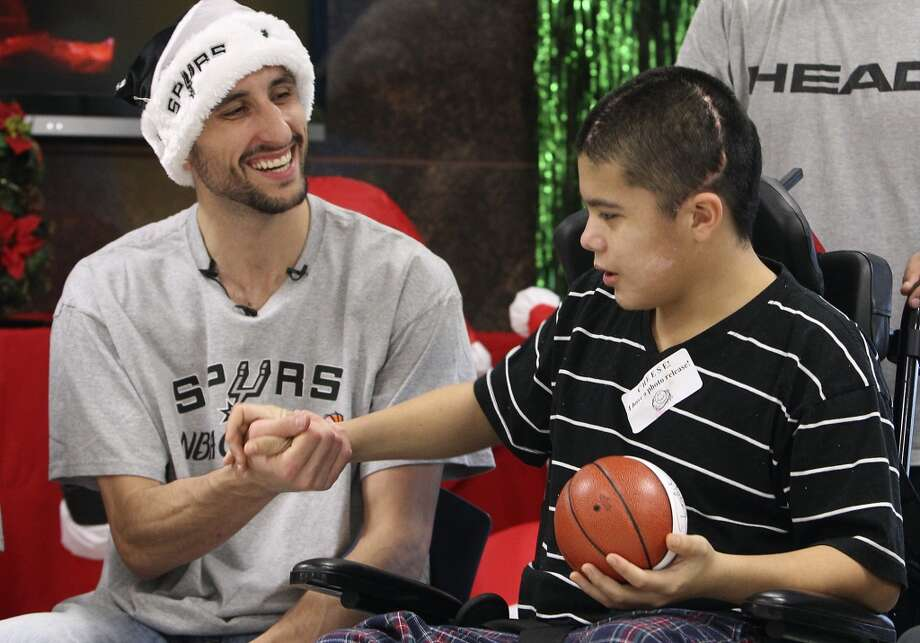 Moises Sandoval shakes hands with Spurs guard Manu Ginobili during a visit with Spurs players including Spurs center-forward Boris Diaw (right) at the Children's Hospital of San Antonio on Tuesday, Dec. 4, 2012.  (Kin Man Hui / San Antonio Express-News)