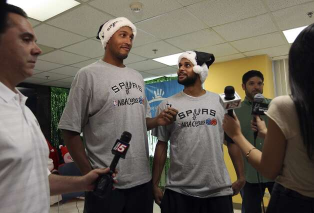 Spurs players Boris Diaw (second from left) and Patty Mills share a lighter moment before chatting with the media after they along with teammate Manu Ginobili met and took photos with young patients at the Children's Hospital of San Antonio on Tuesday, Dec. 4, 2012.  (Kin Man Hui / San Antonio Express-News)