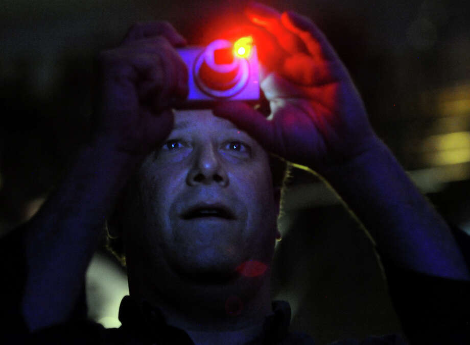 Dave Rubin, of Stamford, snaps photos as he watches Neil Young perform in concert at the Webster Bank Arena in Bridgeport, Conn. on Tuesday December 4, 2012. Photo: Christian Abraham / Connecticut Post