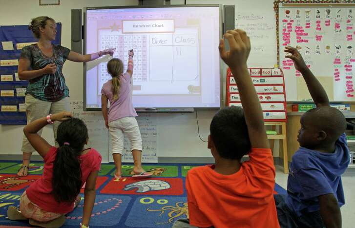 First grade teacher, Susanne Oliver, instructs Jesica Evans, 7, at a SMART Board, an interactive whiteboard, during summer school at Lovett Elementary, 8814 South Rice Ave.