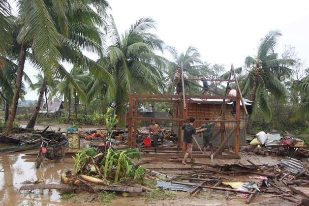 Residents repair their damaged homes after Typhoon Bopha made landfall in Compostela Valley in southeastern Philippines Tuesday Dec. 4, 2012. Typhoon Bopha (local name Pablo), one of the strongest typhoons to hit the Philippines this year, barreled across the country's south on Tuesday, killing at least 40 people and forcing more than 50,000 to flee from inundated villages.  (AP Photo/Karlos Manlupig) Photo: Karlos Manlupig