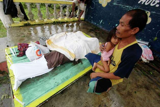 A resident cuddles his child next to the bodies of three children who were killed in a landslide that swept their home after Typhoon Bopha made a landfall in Compostela Valley in southeastern Philippines Tuesday, Dec. 4, 2012. Typhoon Bopha , one of the strongest typhoons to hit the Philippines this year, barreled across the country's south on Tuesday, killing dozens of people and forcing more than 50,000 to flee from inundated villages. (AP Photo/Karlos Manlupig) Photo: Karlos Manlupig