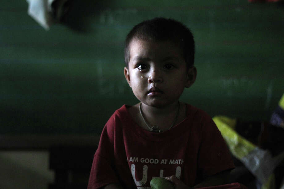 A boy waits in a temporary shelter after Typhoon Bopha made landfall in Compostela Valley in southeastern Philippines Tuesday Dec. 4, 2012. Typhoon Bopha (local name Pablo), one of the strongest typhoons to hit the Philippines this year, barreled across the country's south on Tuesday, killing at least 40 people and forcing more than 50,000 to flee from inundated villages. (AP Photo/Karlos Manlupig) Photo: Karlos Manlupig