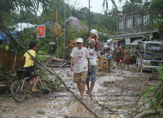 Residents walk back to their homes after Typhoon Bopha made landfall in Compostela Valley in southeastern Philippines Tuesday Dec. 4, 2012.  Typhoon Bopha (local name Pablo), one of the strongest typhoons to hit the Philippines this year, barreled across the country's south on Tuesday, killing at least 40 people and forcing more than 50,000 to flee from inundated villages.  (AP Photo/Karlos Manlupig) Photo: Karlos Manlupig