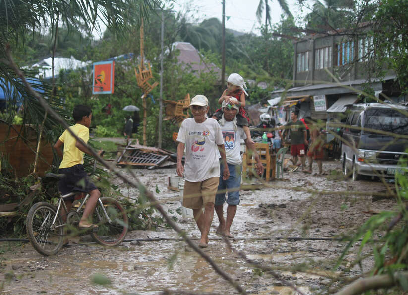 Residents walk back to their homes after Typhoon Bopha made landfall in Compostela Valley in southea