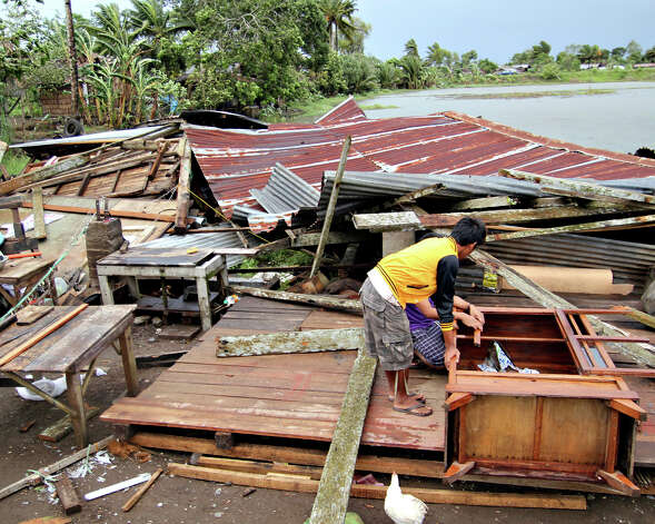 Residents prepare to assess their house which was damaged by Typhoon Bopha in Butuan city in southeastern Philippines Tuesday Dec. 4, 2012. A Philippine governor says at least 33 villagers and soldiers have drowned when torrents of water dumped by the powerful typhoon rushed down a mountain, engulfing the victims and bringing the death toll from the storm to about 40. (AP Photo/Erwin Mascarinas) Photo: Karlos Manlupig