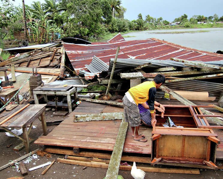 Residents prepare to assess their house which was damaged by Typhoon Bopha in Butuan city in southea