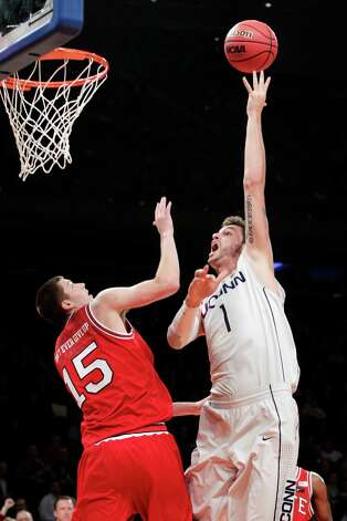 Connecticut's Enosch Wolf (1) shoots over North Carolina State's Scott Wood (15) during the first half of their NCAA college basketball game in the Jimmy V Classic at Madison Square Garden, Tuesday, Dec. 4, 2012, in New York. (AP Photo/Frank Franklin II) Photo: Frank Franklin II, Associated Press / AP