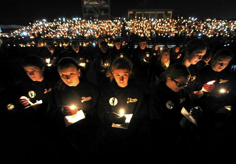 Member of the Capital District Crossfire girls softball team and teammates of Deanna Rivers join thousands during a candlelight vigil and memorial service for the Shen crash victims at Shenendehowa High School in Clifton Park, NY Tuesday Dec. 4, 2012. Shen students Chris Stewart and Deanna Rivers died in the crash with  Matt Hardy and Bailey Wind being seriously injured.(Michael P. Farrell/Times Union) Photo: Michael P. Farrell