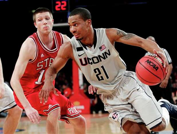 UConn's Omar Calhoun (21) drives past  North Carolina State's Scott Wood (15) during the first half of their  NCAA college basketball game in the Jimmy V Classic at Madison Square  Garden, Tuesday, Dec. 4, 2012, in New York. (AP Photo/Frank Franklin II)