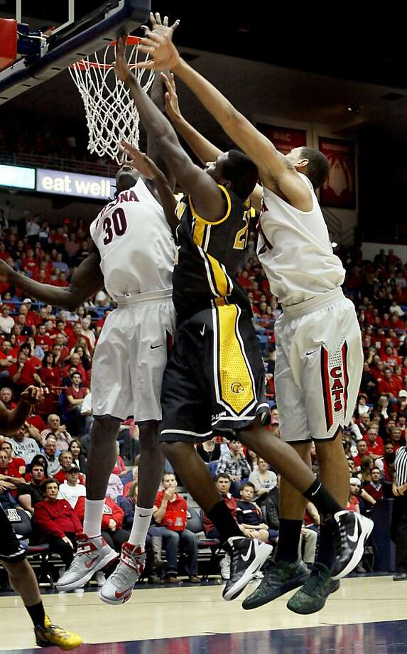Norville Carey squeezes between Arizona's Angelo Chol (30), Brandon Ashley. Photo: Wily Low, Associated Press