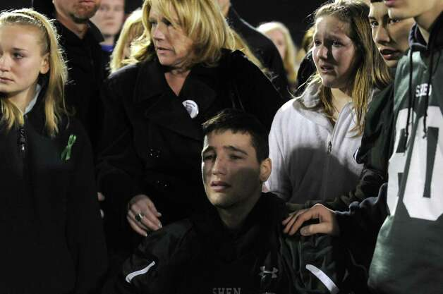 Crash survivor Matt Hardy, center, is surrounded by family, friends and football teammates after arriving by medical van during a candlelight vigil and memorial service for the Shen crash victims at Shenendehowa High School in Clifton Park, NY Tuesday Dec. 4, 2012. Shen students Chris Stewart and Deanna Rivers died in the crash with Matt Hardy and Bailey Wind being seriously injured.(Michael P. Farrell/Times Union) Photo: Michael P. Farrell