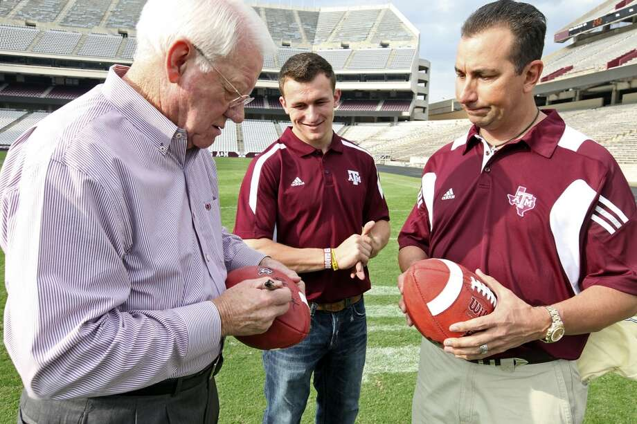 Former Texas A&M running back John David Crow, who won the 1957 Heisman Trophy, autographs footballs as current Texas A&M freshman quarterback Johnny Manziel, who is a Heisman finalist, and his dad Paul Manziel look on after a portrait session Tuesday, Dec. 4, 2012, at Kyle Field in College Station.