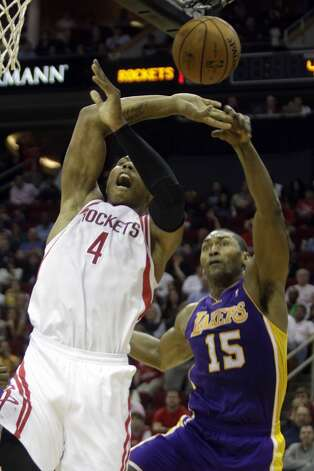 Rockets center Greg Smith is fouled by Metta World Peace of the Lakers on a shot attempt. (Melissa Phillip / Houston Chronicle)