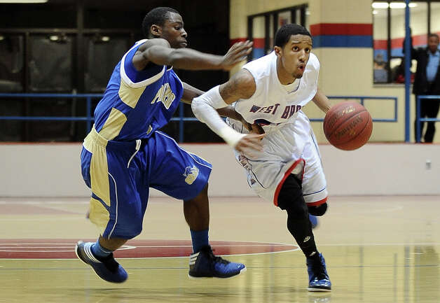West Brook Bruin Jordan Green, #24, fights his way down the court past Ozen Panther Kourtney Williams, #4, during the West Brook high school basketball game against the Ozen  on Tuesday December 4, 2012, at West Brook High School. West Brook won over Ozen 52 - 46. Photo taken: Randy Edwards/The Enterprise Photo: Randy Edwards