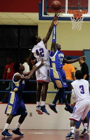 West Brook Bruin Jjuan Hadnot, #42, puts two on the board with his assist to tip the ball in during the West Brook high school basketball game against the Ozen  on Tuesday December 4, 2012, at West Brook High School. West Brook won over Ozen 52 - 46. Photo taken: Randy Edwards/The Enterprise Photo: Randy Edwards