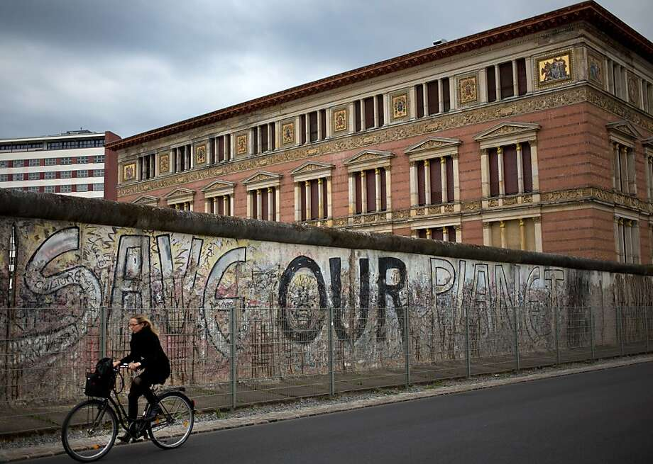 A woman cycles past a surviving part of the Berlin Wall; the Martin-Gropius-Bau gallery is in the background. Most of the wall came down in 1989, signaling the end of the Cold War. Photo: David Gannon, AFP/GettyImages