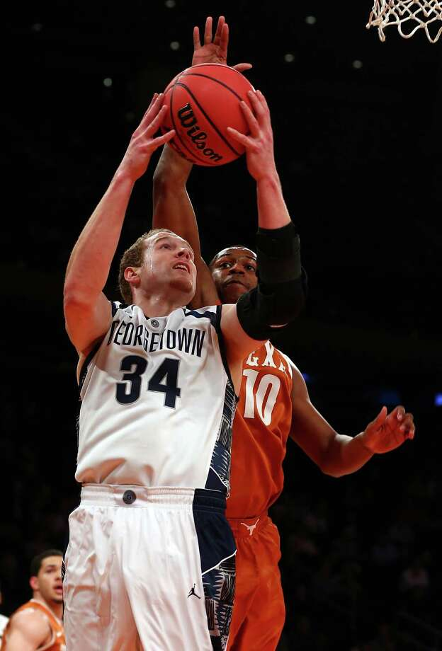 Nate Lubick #34 of the Georgetown Hoyas takes a shot as Jonathan Holmes #10 of the Texas Longhorns defends during the Jimmy V Classic on December 4, 2012 at Madison Square Garden in New York City. Photo: Elsa, Getty Images / 2012 Getty Images