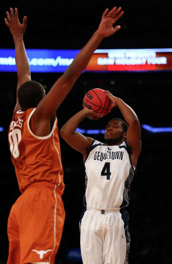 D'Vauntes Smith-Rivera #4 of the Georgetown Hoyas takes a shot as Jonathan Holmes #10 of the Texas Longhorns defends during the Jimmy V Classic on December 4, 2012 at Madison Square Garden in New York City. Photo: Elsa, Getty Images / 2012 Getty Images