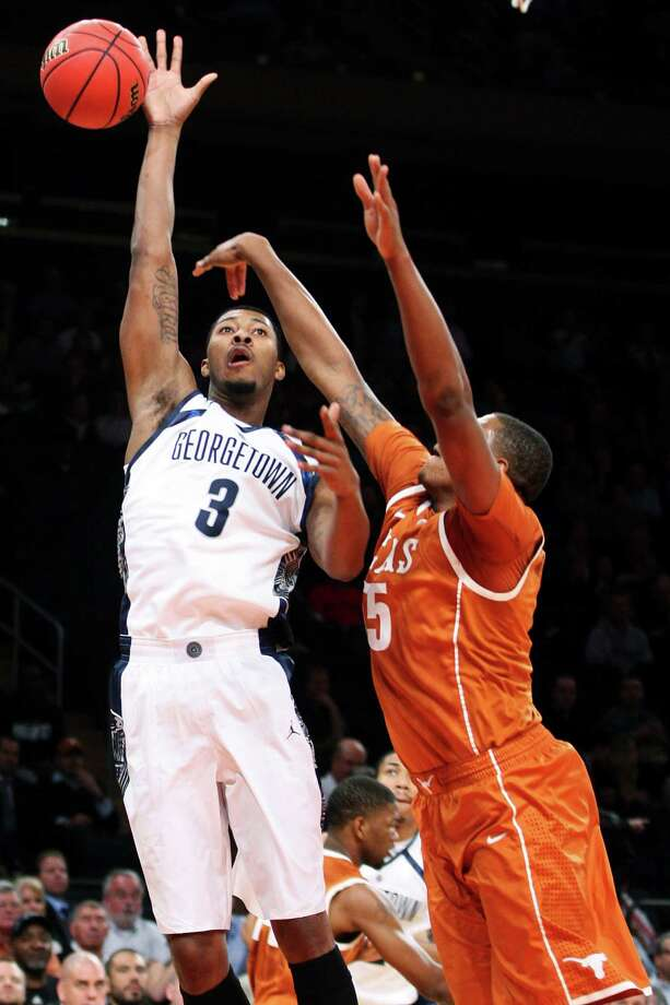 Georgetown's Mikael Hopkins (3) shoots over Texas' Cameron Ridley (55) during the first half of their NCAA college basketball game in the Jimmy V Classic, Tuesday, Dec. 4, 2012, at Madison Square Garden in New York. (AP Photo/Frank Franklin II) Photo: Frank Franklin II, Associated Press / AP