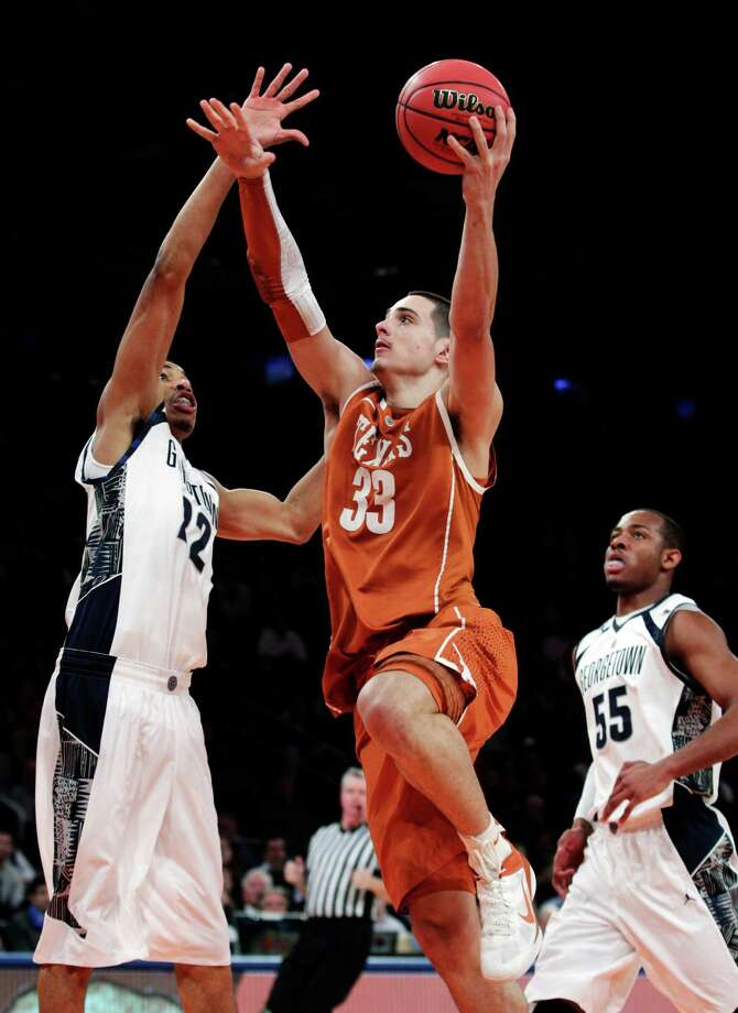 Texas' Ioannis Papapetrou (33) drives past Georgetown's Otto Porter (22) during the second half of their NCAA college basketball game in the Jimmy V Classic at Madison Square Garden, Tuesday, Dec. 4, 2012, in New York. Georgetown won 64-41. Photo: Frank Franklin II, Associated Press / AP