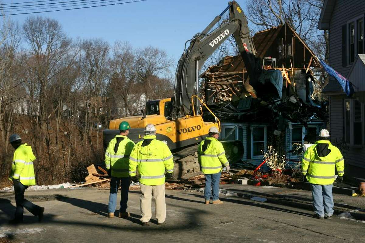 A home on 161 North Oak Drive in Shelton is demolished on Friday, Dec. 18, 2009. The vacant home was in danger of collapsing after a mudslide and posed a threat to the Riverview Condominium complex below it.