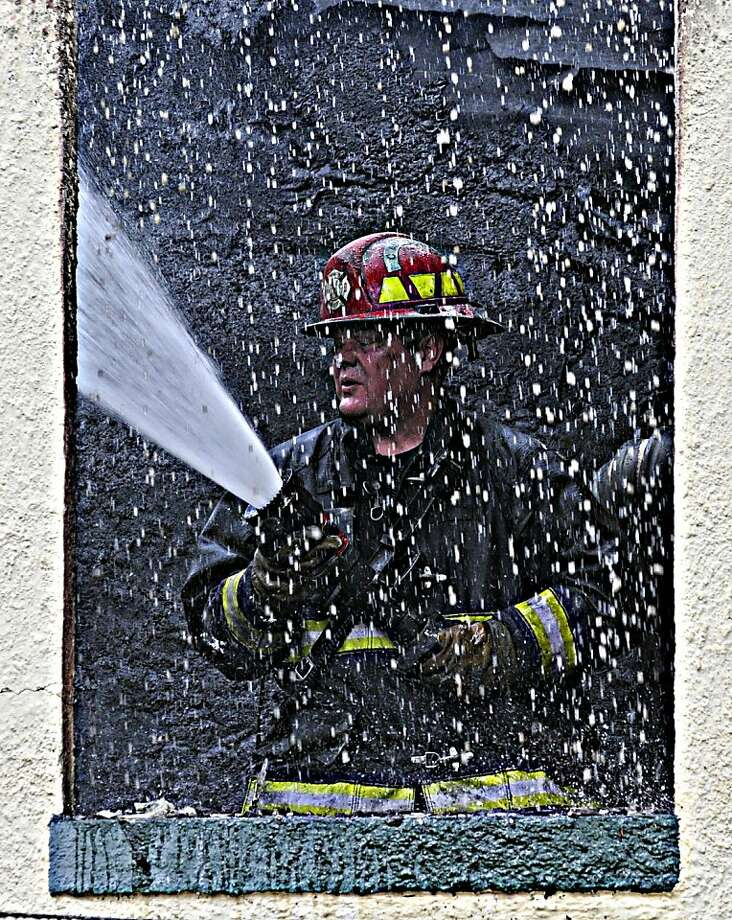 A firefighter is seen in a window as he fights a fire at an apartment building in Charleston, W. Va., Monday Dec. 3, 2012.  The fire left several people homeless but did not injure anyone. Photo: Tom Hindman, Associated Press